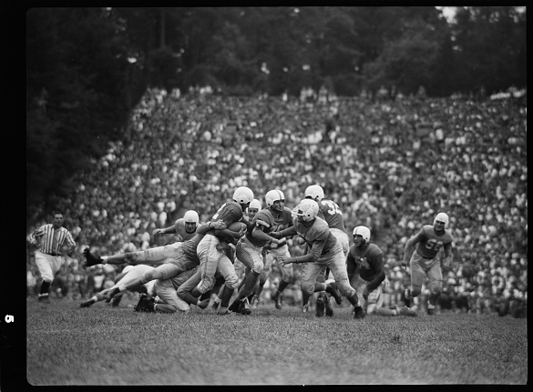 "Despite being slightly out of focus, Wilmington's Sunday Star-News and The Charlotte News for Tuesday September 27th printed this photograph of Texas quarterback Paul Campbell being ""smothered by Tar Heel tacklers."" Bob Cox is identified as blocking Campbell's path, and the only Longhorn is identified as Ferrell (#36)."