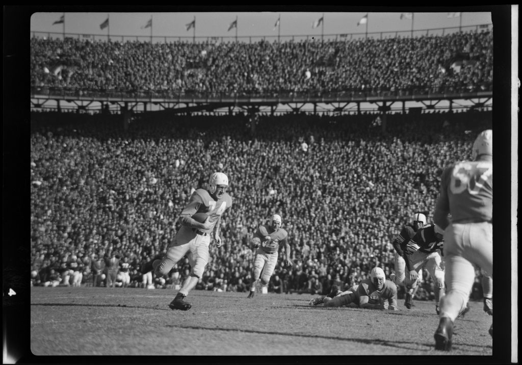 The Greensboro Daily News published this Hugh Morton photograph (cropped similarly as seen below) of Bob Kennedy (#74) scampering a double reverse for nine yards and a first down. In the center of the photograph is blocking back Eddie Knox (#34).