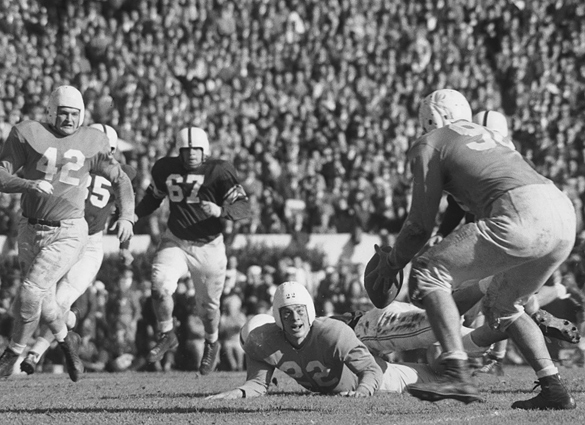 Chan Highsmith catches a lateral from Charlie Justice (on the ground). Also in the photograph is Ted Hazelwood (#42) and Oklahoma's Buddy Burris (#67), who made the tackle on the play. Published in several newspapers with different cropping, this print is cropped by this blog's editor.