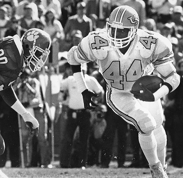 UNC running back Kelvin Bryant running with the football against Clemson at Clemson University, November 6, 1980. UNC won the game 24-19. The 1980 Tar Heels finished the regular season with an 11-1 record and the ACC Championship—the last time UNC won the title. The Tar Heels then played a postseason game on December 31st in Houston, where they defeated Texas 16 to 7 in the Bluebonnet Bowl. (Photograph by Hugh Morton, cropped by the editor.)
