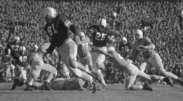 UNC's Johnny Clements (#20) tackling Oklahoma running back George Thomas (#25) with the ball during the third quarter. Other Oklahoma players are #70 tackle Wade Walker, #67 guard Paul Burris, #40 fullback Leon Heath, #81 end Jimmy Owens, and #26 quarterback Jack Mitchell. UNC players are #62 left guard Bill Wardle and #51 right tackle Len Szafaryn.