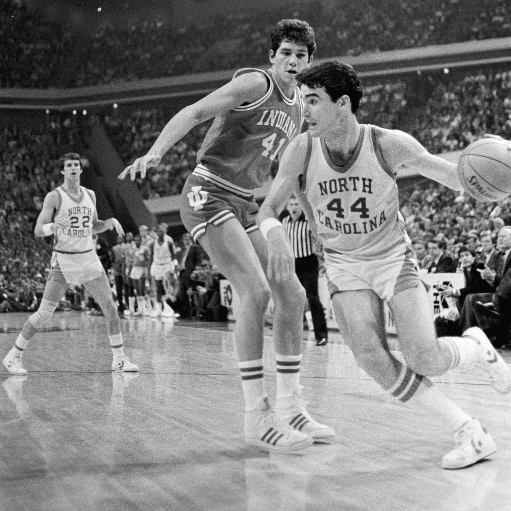 Matt Doherty dribbles toward the lane while Indiana forward Mike Giomi defends. Tar Heel guard Buzz Peterson looks on, (Photograph by Hugh Morton, cropped by the author.)
