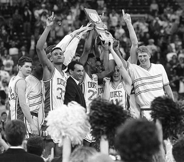 1991 NCAA Men's Basketball Champions Duke Blue Devils celebrating with trophy, in Indianapolis, IN. L to R on podium: #5 Bill McCaffrey, #32 Christian Laettner (background), #33 Grant Hill, Head Coach Mike Krzyzewski, #23 Brian Davis, #12 Thomas Hill, #11 Bobby Hurley, and Clay Buckley (far right).