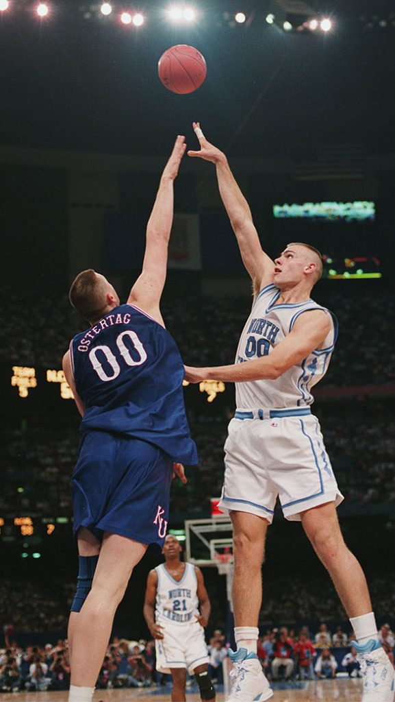 Tar Heel Eric Montross lofts a shot as Kansas Jayhawk Greg Ostertag defends during the 1993 NCAA Men's Division I Basketball Tournament National Semifinal matchup. Will the Tar Heels and Kansas face one another again in 2016? (Hugh Morton photograph cropped by the author.)