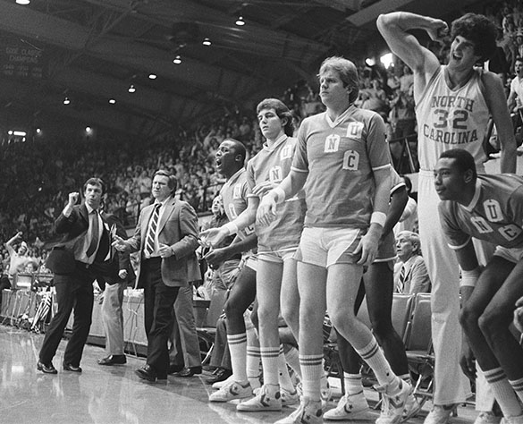 The anguished facial expression of UNC Head Basketball Coach Dean Smith (second from left) makes you wonder if assistant coach Roy Williams, far left, is doing his happy dance . . . or not . . . during UNC's 1982 East Regional Final played at Reynolds Coliseum in Raleigh, North Carolina on March 21, 1982. Others on the UNC bench (L to R) are #54 Warren Martin, #43 Jeb Barlow, #51 Timo Makkomen, #32 John Brownlee, and Warren Martin. (Hugh Morton photograph, cropped by the author.)