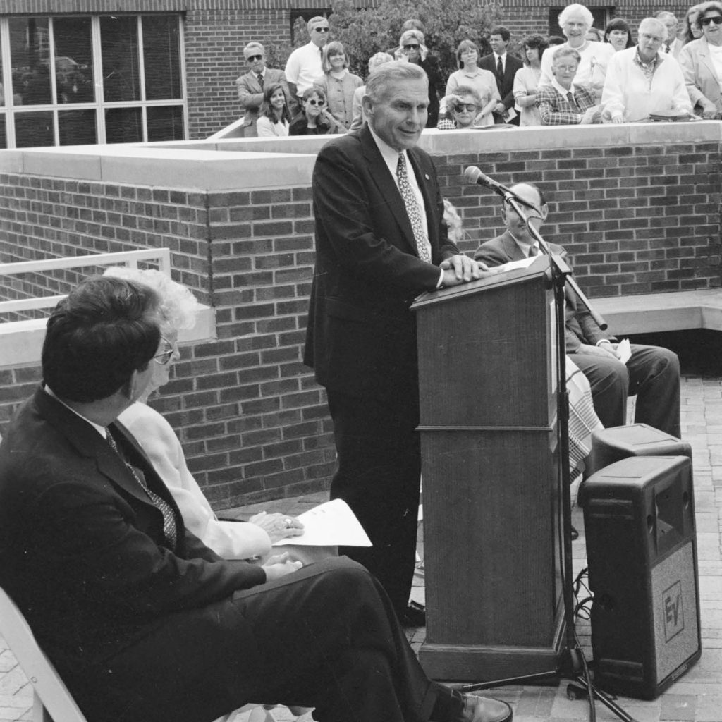 "UNC Chancellor Paul Hardin speaking to gathering at the dedication of the George Watts Hill Alumni Center on May 14, 1993. Seated on the left are General Alumni Executive Director Doug Dibbert, UNC Class of 1970 and outgoing General Alumni President Elizabeth ""Pepper"" Dowd, UNC Class of 1953 (photograph cropped by editor)."
