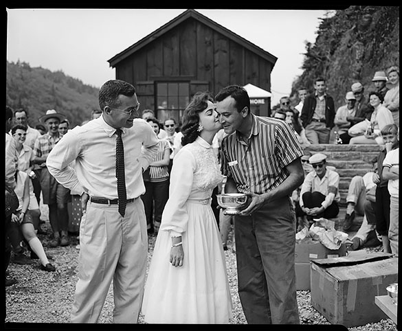 "Spectators watching woman kissing man on cheek who is receiving trophy, probably for winning the Sports Car Hill Climb event at Grandfather Mountain, N. C. Golfer Billy Joe Patton at left. From a negative labeled ""Sports Cars '57"" by Hugh Morton."