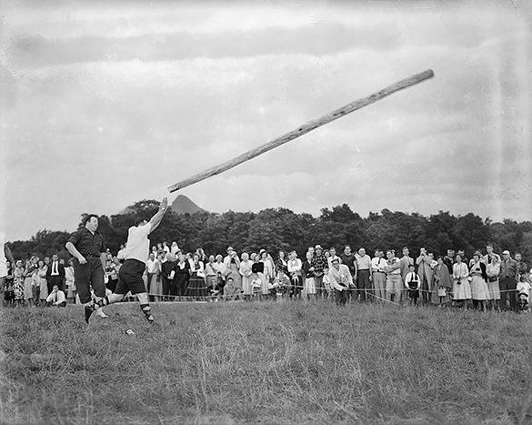 Man tossing caber with spectators in background at the first annual Grandfather Mountain Highland Games in 1956. Notice the caber tosser is in stocking feet and that the judge is barefooted. Photograph by Hugh Morton.