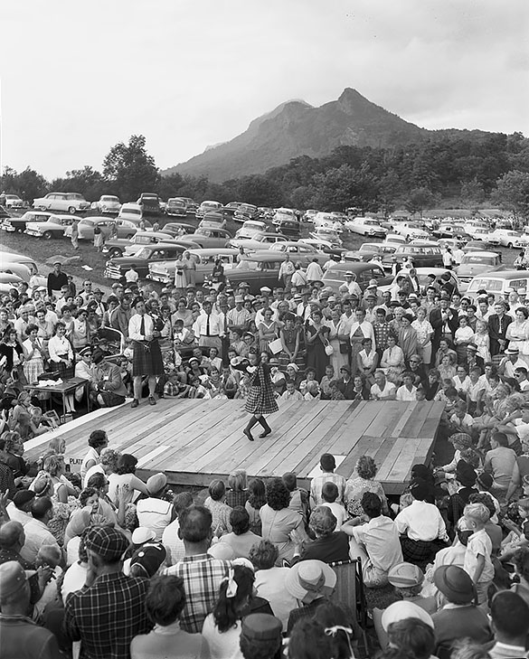 Girl in Scottish attire dancing on a wooden platform, with crowd watching and Grandfather Mountain in the background, during the 1956 Grandfather Mountain Highland Games. Photograph by Hugh Morton.