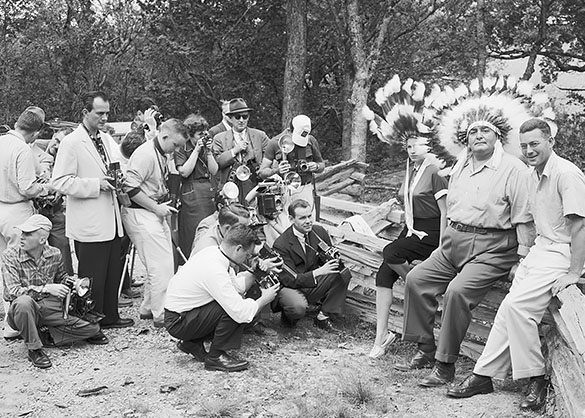 Scene photographed by Hugh Morton during a Grandfather Mountain Camera Clinic sometime in the early 1950s as attendees practice their portraiture technique. The photographers' models are (left to right) an unknown woman in Indian headdress, Osley Bird Saunooke, Chief of the Eastern Band of the Cherokee Indians from 1951-1955, and golfer Billy Joe Patton. Grandfather Mountain still runs the clinic, which was held there last weekend. (Photograph cropped by editor.)