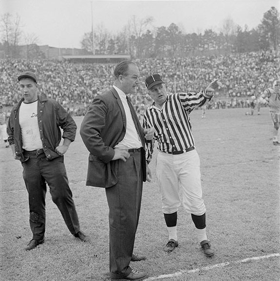 "Duke head coach Bill Murray receives an explanation from a referee—probably after Max Chapman's filed goal as the frame below is the next image on the roll of film. According to the High Point Enterprise sports write Bob Hoffman, ""In a matter of seconds after UNC's Max Chapman booted a 42-yard filed goal . . . Murray had charged onto the field and was chin-to-chin with one of the officials."" Murray said the clock didn't stop after the field goal. The official contended that only six seconds clicked off the clock. Murray disagreed because, as he explained after the game, ""I had gotten together a group of players to go back into the game, talked to the quarterback, run out onto the field and got the official's attention to stop the clock. I just can't move that fast."" (Scan of Hugh Morton's negative is shown full frame.)"