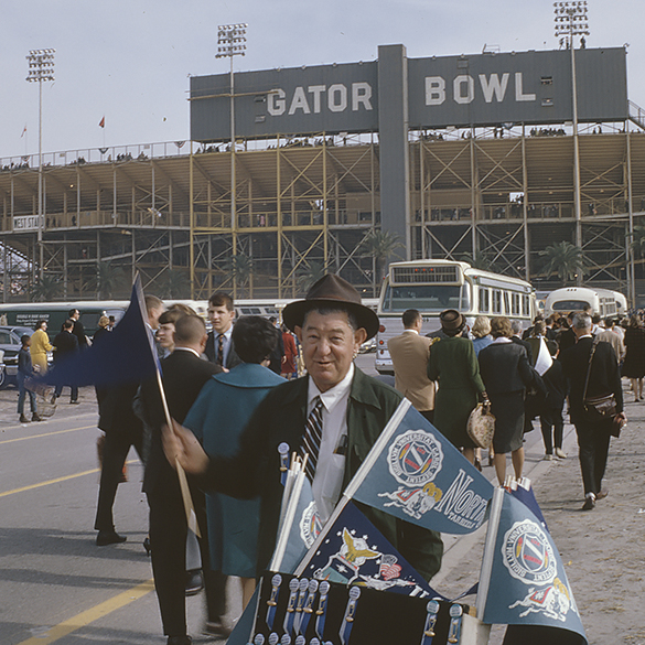 Souvenir seller outside the Gator Bowl in 1963. Photograph by Hugh Morton, cropped from a 35mm color slide by the editor.