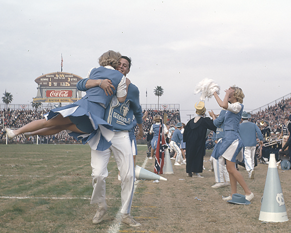 With the scoreboard reading 26-0 in the third quarter, a UNC male cheerleader, donning a now-classic sweater, swings his partner 'round and 'round during a moment on the playing field worth swirling about. Photograph by Hugh Morton, cropped from a 35mm slide by the editor.