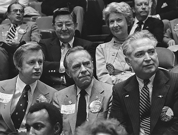 (L to R, Front Row): NC Governor Jim Hunt, NC Lt. Gov. Jimmy Green, and unidentified. Behind them are UNC President William Friday, and Friday's wife Ida. NCAA Championship, Louisiana Superdome, New Orleans, 29 March 1982. (Cropped by the author.)