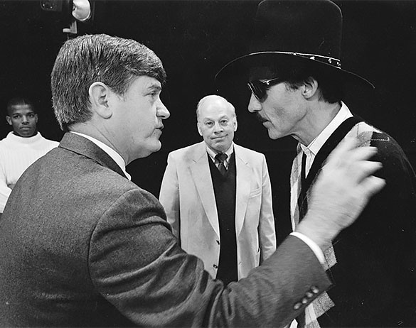 Governor Jim Martin confers with Richard Petty, as Charlie Justice looks on. Duke basketball star Tommy Amaker may be the person on the far left. (Photograph cropped by the editor.)
