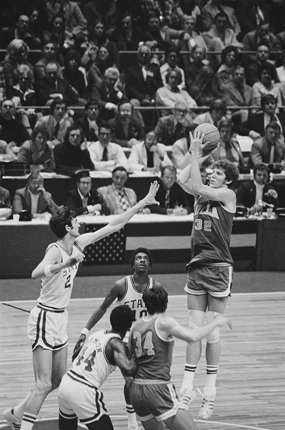 UCLA All America center Bill Walton shoots over the outstretched arm of NC State's Tommy Burleson, as NC State's Moe Rivers (#10) focuses on Walton. In the foreground, NC State's David Thompson tries to out position UCLA's Dave Meyers. Hugh Morton's game-action photographs focused on the two seven-foot centers, this being his best shot.