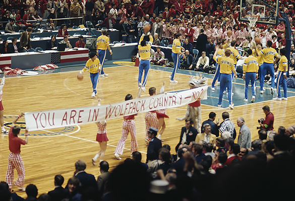 """NC State cheerleaders displaying a banner that reads""""You are in Wolfpack Country"""" before the start of the NC Stave versus UCLA 1974 NCAA Mens' Basketball National Semifinal at the Greensboro Coliseum, on March 23."""