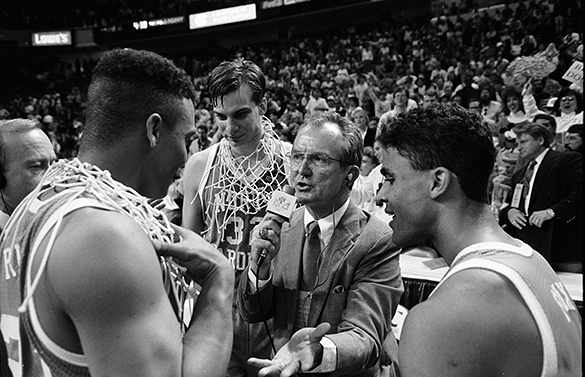 Woody Durham interviews King Rice following win over Duke in the 1991 ACC Tournament. Also in the frame is #32 Pete Chilcutt, and Rick Fox (right). Jim Heavner, Tar Heel Sports Network and CEO of The Village Companies of Chapel Hill can be partially seen in extreme left of the frame.