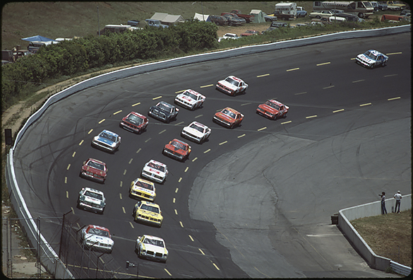 Neil Bonnett in car number 75 (front left) and car number 7, which in the World 600 would have been Kyle Petty, lead a pack of fourteen cars, with car number 32 separated from the pack ahead.