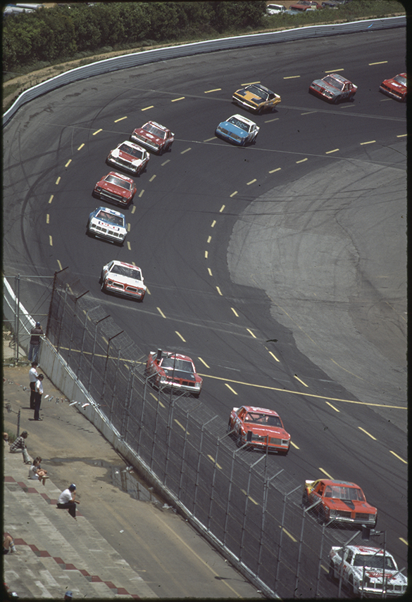 Slide number #19 depicts a pack exiting turn four lead by car 23, followed by cars 34, 76, and 5.