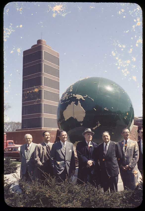 North Carolina Governor Luther Hodges and several unidentified men pose in front of the globe on the grounds of S. C. Johnson and Sons Company in early May 1958. Frank Lloyd Wright was the architect for The Research Tower, opened in 1950, seen in the background. Photograph by Hugh Morton, May 1 or 2, 1958.