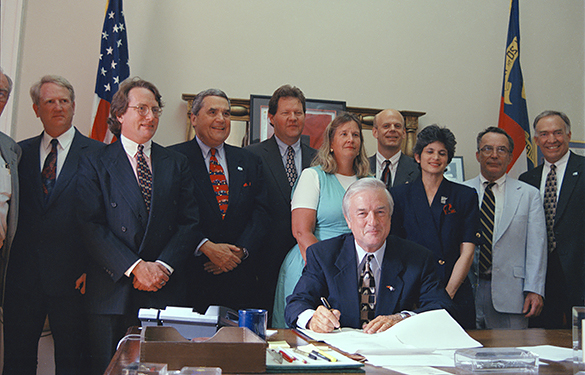 "North Carolina Governor Jim Hunt signing the ""Gorges Bill"" on July 8, 1997. The second (fully visible) person from the left is R. Michael Leonard, recognized from another Morton image in the online collection and confirmed by a quote in the Asheville Times. At the time Leonard was an attorney with the firm Womble, Carlyle, Sandridge, and Rice. The others in the photograph are unidentified."