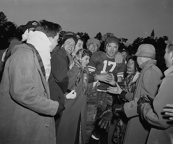 Scan of Hugh Morton's negative (as shot) of Duke's Billy Cox holding the game ball after a 7-0 win over UNC at Kenan Stadium, 25 November 1950. This image appears in the sports sections of the Wilmington Morning Star and the Charlotte News. The latter identified the woman next to Cox as Mona Booth, Miss Durham of 1950. Other Morton photographs appeared in those newspapers (shown below), but the negatives either have not yet been located in the collection or have not survived.