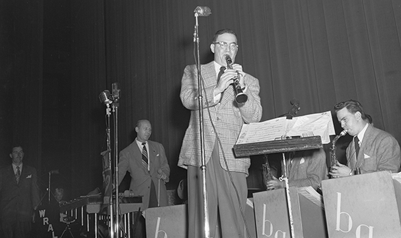 A SECOND MYSTERY—Benny Goodman, front and center, playing clarinet as captured in Hugh Morton's unidentified negative (the top portion of the image is cropped here). Morton mentions in his 1988 book Making a Difference in North Carolina that he went to a Goodman concert in Raleigh. This previously unscanned negative has a WRAL banner displayed on stage (lower left). Piecing together clues from the sheet music on Goodman's music stand in this and three other negatives, coupled with Goodman's touring history and list of band members, unlocks part of the mystery. That's Red Norvo at the vibraphone behind Goodman.
