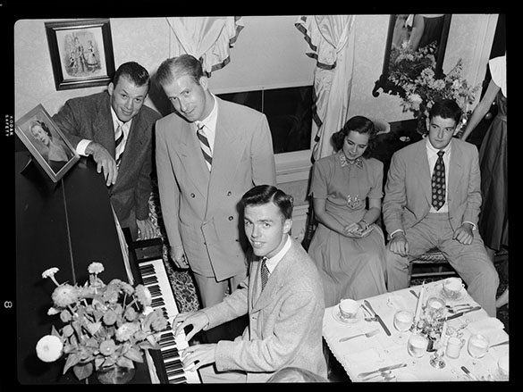 "ONE SONG LEADS TO ANOTHER—Charlie Justice (left) stands next to Orville Campbell beside a piano at an unknown event. The State published a tightly cropped headshot of these two gentlemen in its September 15, 1951 issue of the magazine. The photograph accompanied an article titled ""Yankeeland Hears 'It'"" about Campbell and Hank Beebe's song, ""Way Up in Carolina."" The caption in The State reads, ""Charlie Justice, subject of Orville Campbell's first popular song, ""All the Way Choo-Choo."" Charlie owned a piece of that song, but didn't make any money. (Morton Photo)"" Another mystery, however, appeared when viewing the full negative, which has no accompanying information. Is that Hank Beebe on piano? We believe so. The occasion? Still unknown."