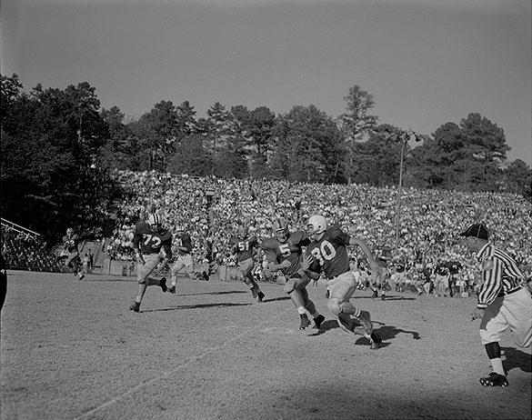 "Another Morton photograph, cropped on the runner and two pursuers, published by The Charlotte News, and captioned ""WHILE THE MOMENTS WERE STILL GLORIOUS North Carolina's Ed Sutton gains 11 yards to the Notre Dame six-yard line in the second quarter before being hauled down by Paul Nornung (5) closing in."" Fans of the era will quickly recognize that typo because he is Paul Hornung, the 1956 Heisman Trophy winner and later NFL Hall of Fame star for the Green Bay Packers."