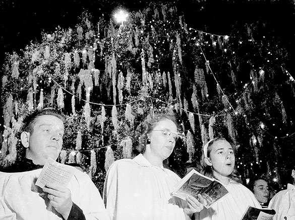 "Men and women singing Christmas carols in front of the ""World's Largest Living Christmas Tree"" in Hilton Park, Wilmington, NC. A very similar photograph appears in ""The Duke Power Company Quiz"" magazine advertisement in the 15 December 1951 issue of The State."