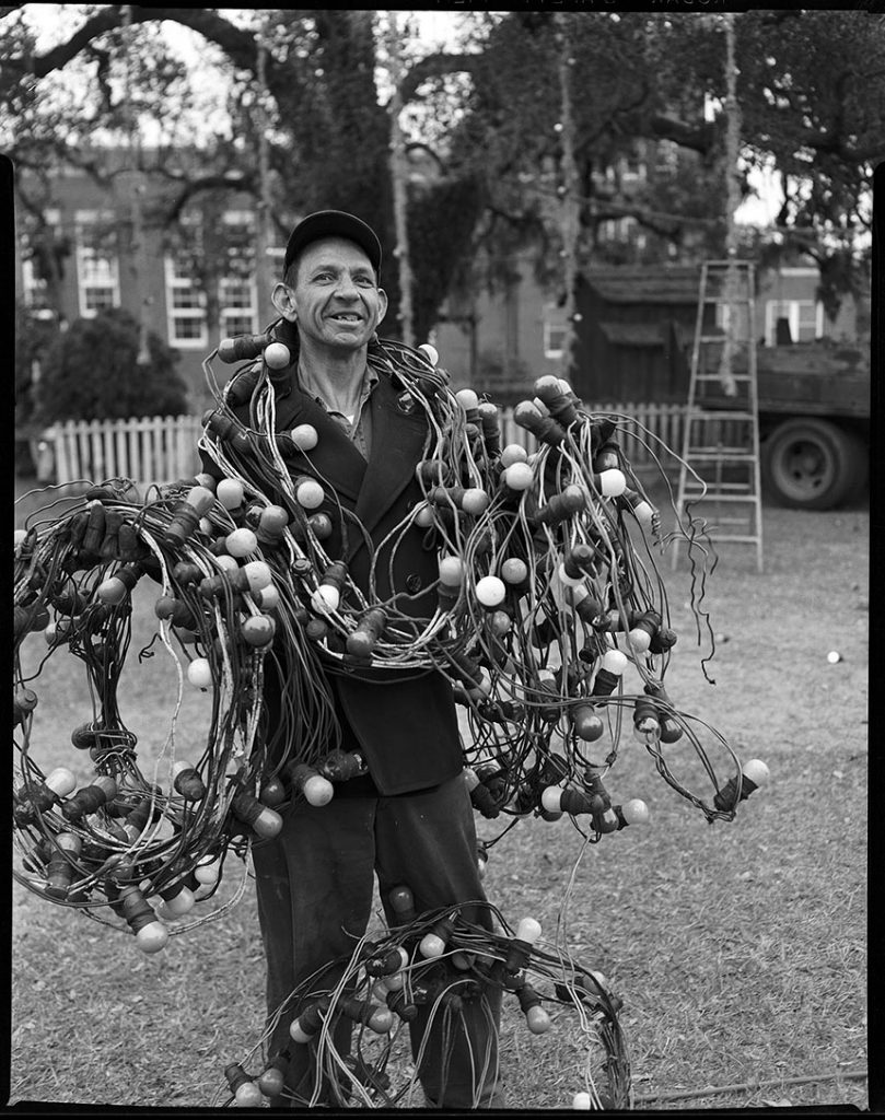 "Portrait of Arthur Sandlin standing outdoors with arms full of Christmas lights, probably used or to be used for the purpose of adorning the ""World's Largest Living Christmas Tree."""