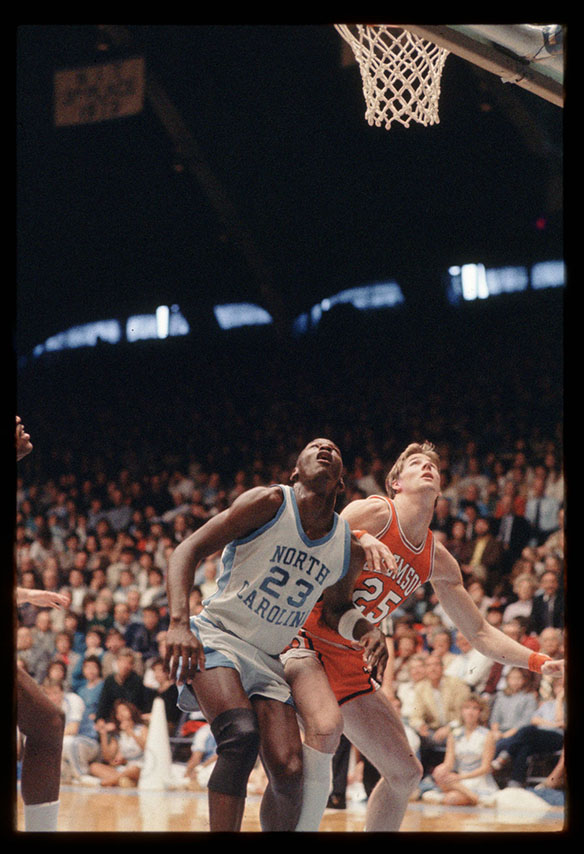 UNC legend Michael Jordan and possibly Murray Jarman look skyward in anticipation of action above the basket. The year of this image is not known.