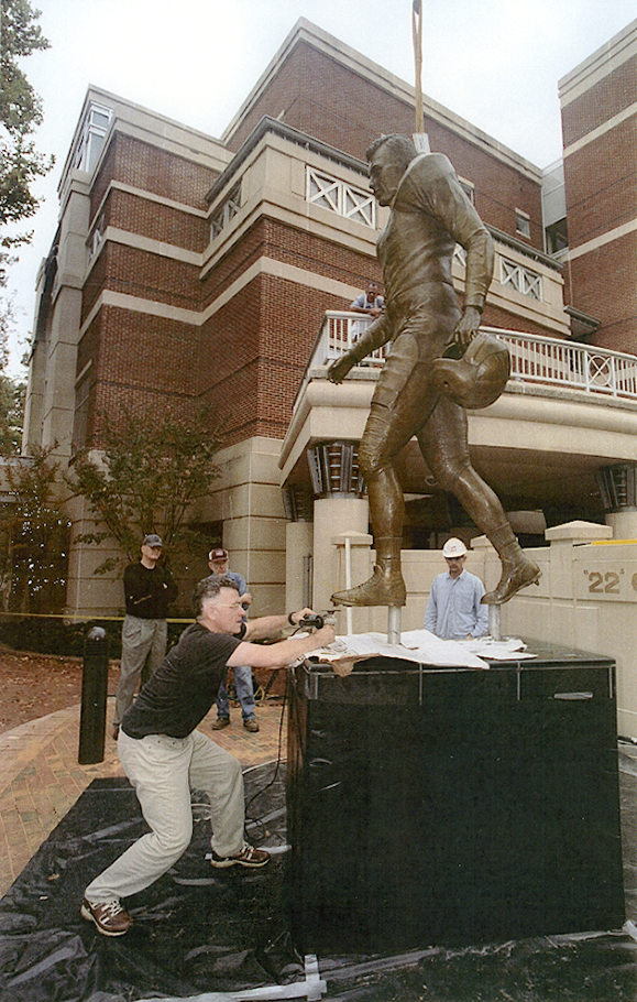 Johnpaul Harris making a final adjustment during installation of the Charlie Justice statute near Kenan Memorial Stadium, November 3, 2004.