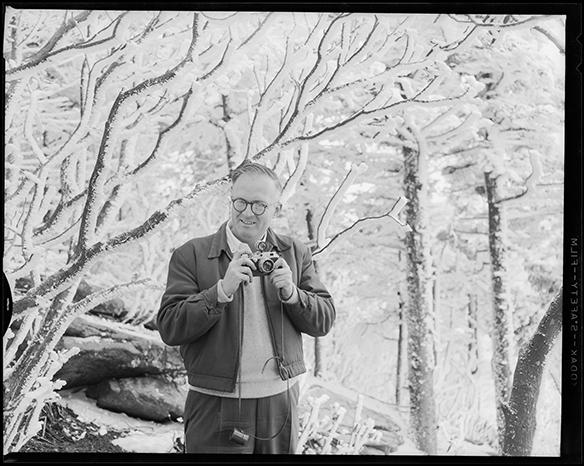 Hugh Morton posed holding camera in snowy scene