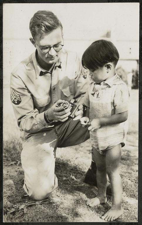 Hugh Morton showing his camera to a child