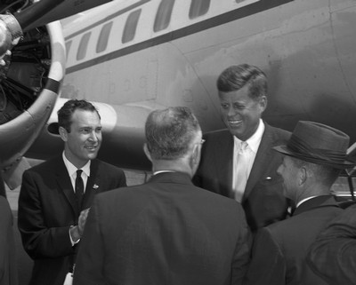 Senator Kennedy is greeted by a group of men, including U.S. Representative (6th District-N.C.) Horace Kornegay (far left), as he steps off airplane.