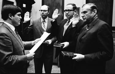 "James ""Jim"" E. Long (center) takes oath of office for North Carolina House of Representatives (representing Alamance County) at a local ceremony in January of 1971.  Pictured with him are State Representative W.S. Harris Jr. (l) and State Senator Ralph Scott (r)."