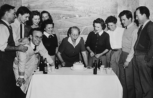 "As captioned in Light and Air: The Photography of Bayard Wootten, ""The staff of the Wootten-Moulton Chapel Hill studio joined Wootten in a birthday celebration about 1940. George C. Moulton, her half brother, stands on the far left. In front of him and leaning over the table is T. C. Moore, Wootten's successor in the business. Margaret Howland Fowler, a secretary in the studio for two decades, is to Wootten's right. (Mary Moulton Barden Collection)"""