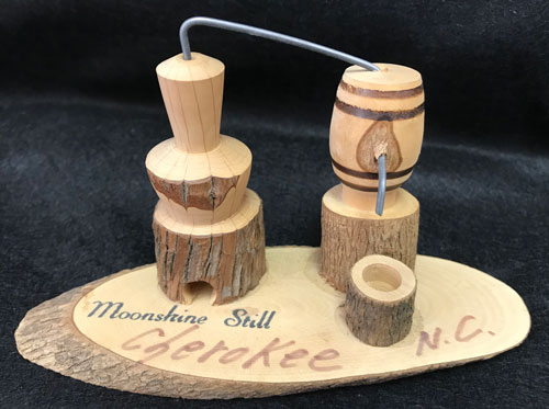 "Carved wooden model of a still with words ""Moonshine Still, Cheroke, N.C."""