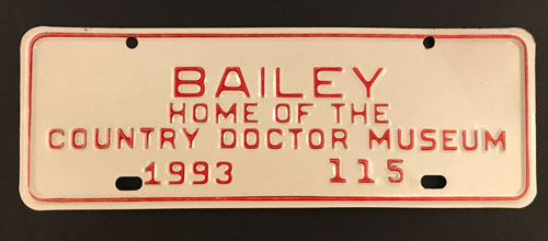 "Front license plate reading ""Bailey, Home of the Country Doctor Museum."""