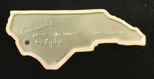 """Verso of Hylan dish shaped like North Carolina, with """"Emrich's State of the Union by Hyaln"""" stamped on it."""