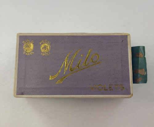 Closed box of Milo Violets cigarettes with name of cigarettes in cursive on case top