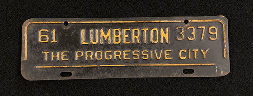 "Front license plate with the words ""Lumberton, The Progressive City."""