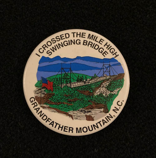 "Pinback featuring a colored image of the swinging bridge and the words ""I crossed the Mile High Swing Bridge. Grandfather Mountain, N.C."""