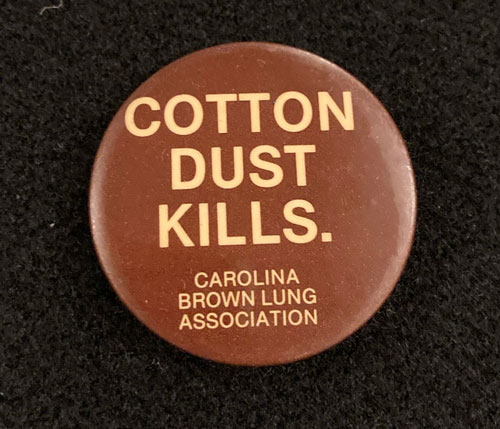 """Burgundy pinback with the words, """"Cotton Dust Kills. Carolina Brown Lung Association."""""""