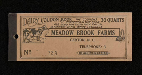 """The cover of a book of milk coupons. It includes an illustration of a cow and the words """"Thirty quarts. The coupons in this book are good for the face value in payment of all dairy products. Meadow Brook Farms. Gerton, N.C. Telephone three."""""""