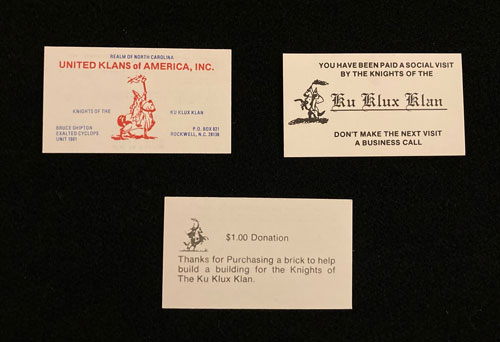 """Three business cards for Ku Klux Klan organizations. One card includes the words """"Realm of North Carolina, United Klans of America,"""" an illustration of a Klansman on horseback and a name and address in Rockwell, NC. A second card also includes an illustration of a klansman on horseback and a message that reads, """"You have been paid a social visit by the Knights of the Ku Klux Klan. Don't make the next visit a business call."""" The third card includes an illustration of a Klansman on horseback and the message, """"one dollar donation. Thanks for purchasing a brick to help build a building for the Knights of the Ku Klux Klan."""""""