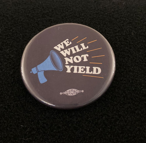 Pinback button with the words we will not yield and an image of a megaphone.