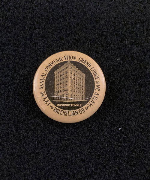 Pinback featuring image of the Masonic Temple and the words 122nd annual commuunication Grand Lodge of N.C.A.F and A.M., Raleigh, January 09.